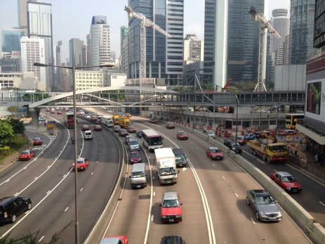 Cars driving on left side of the road…HK industrial buildings architecture, and constant construction work.
